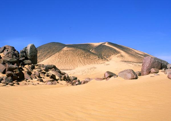 Le volcan sans nom, possédant un cratère de forme égueulée le contraste est saisissant avec le sable qui l'entoure. (Photo : André Laurenti)