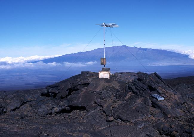 Appareil de surveillance placé sur le Mauna Loa, au loin on remarque le Mauna Kea avec sa forme caractéristique des volcans bouclier. (Photo : André Laurenti)