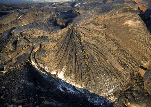 Coulée de lave de type Pahoehoe, un terme hawaiien qui signifie satiné. Elle est caractérisée par une surface lisse, vitreuse, extrêmement coupante, prenant des formes de draperies... (Photo : André Laurenti)
