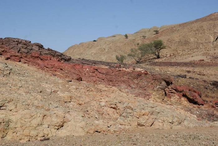 De bas en haut on peut voir des basaltes très altérés, au dessus des radiolarites et le tout recouvert par un nappage de « terre d'ombre ». (Photo : André Laurenti)